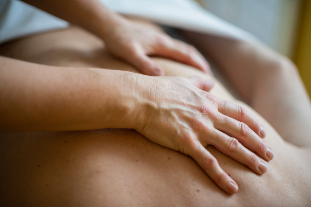 Behandlung mit den Händen am Rücken