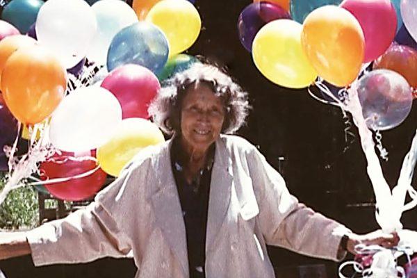 Marion Rosen hält in beiden Händen einen Bund bunter Luftballons